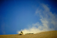 Tractor plowing bare field.