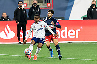 FOXBOROUGH, MA - APRIL 24: Moses Nyeman #27 of D.C. United passes the ball as Carles Gil #22 of New England Revolution defends during a game between D.C. United and New England Revolution at Gillette Stadium on April 24, 2021 in Foxborough, Massachusetts.