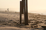 A beach walker checks out debris that washed up on near the Frisco Pier in Frisco, NC, along the Outer Banks after Hurricane Irene on Sunday, Aug. 28, 2011. Photo by Ted Richardson