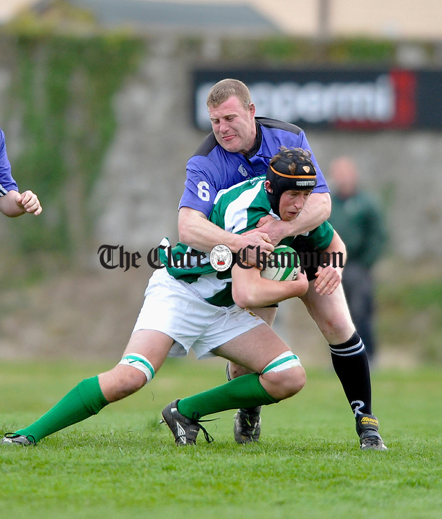 Kilrush's John Galvin gets to grips with Richmond's Ian Madden  during the Webb Cup final at Ennis RFC grounds. Photograph by John Kelly.