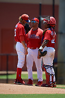 GCL Phillies West pitching coach Bruce Billings (center) talks with pitcher Brandon Ramey (31) and catcher Kevin Escalante (22) during a Gulf Coast League game against the GCL Yankees East on August 3, 2019 at the Carpenter Complex in Clearwater, Florida.  The GCL Yankees East defeated the GCL Phillies West 4-0, the second game of a doubleheader.  (Mike Janes/Four Seam Images)