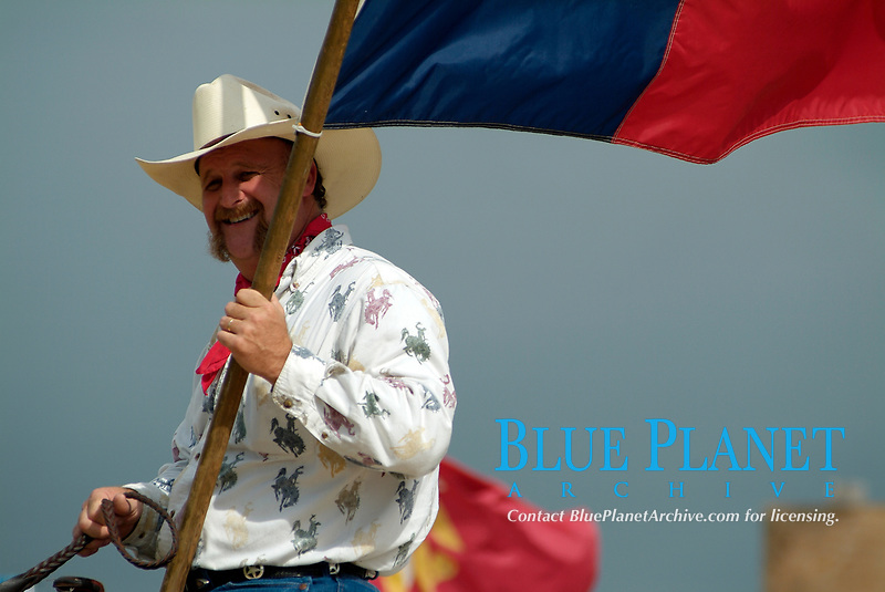 Cowboy riding a horse and carrying the Texan flag during the parade of the annual trailride in Bandera, South of Texas, USA, United States. The Great Western Cattle Trail - also known as the Dodge City Trail and the Old Texas Trail was known for cattle drives including Longhorns to the markets in the eastern part of the USA. The trail began in Bandera County, Texas and ended in Dodge City, Kansas. The entire trail extended from southern Texas to the Canadian border.