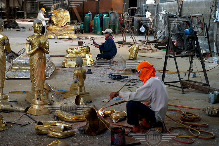 A man welding Buddha statues at Phraruangsamai Buddha Factory.