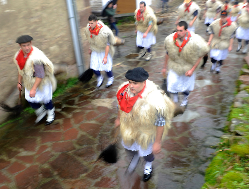 """A group of """"Joaldun"""" march carrying sheep furs and big cowbells on their backs on January 27, 2014 at the village of Ituren, Basque Country. Joaldun groups perform an ancient traditional carnival at the villages of Ituren and Zubieta during two days, carrying sheep furs and big cowbells in their backs and making sound them in order to wake up the earth, to ask for a good new year, a good harvest and also to keep away the bad spirits. (Ander Gillenea / Bostok Photo)"""