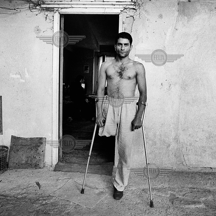 Echmadzin Manvel, an amputee who was one of many thousands of people injured in the Nagorno-Karabakh War (1988–94), stands with the aid of crutches in front of his apartment.<br /><br />The Nagorno-Karabakh Republic (NKR) is a de facto independent republic that came into existence in the early 1990s as a result of the collapse of the Soviet Union. It is not recognised internationally.