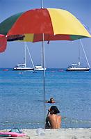 Capo Carbonara, Villasimius (Cagliari), Porto Giunco. Bagnanti in spiaggia, ragazza in topless e ombrellone colorato --- Cape Carbonara, Villasimius (Cagliari), Porto Giunco. Bathers on the beach, a topless girl and a colorful umbrella