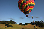 A hot air balloon sails dangerously close to a wire in Napa Valley, CA.