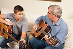 Family at home 16 year old boy playing guitar with his father, and talking to him