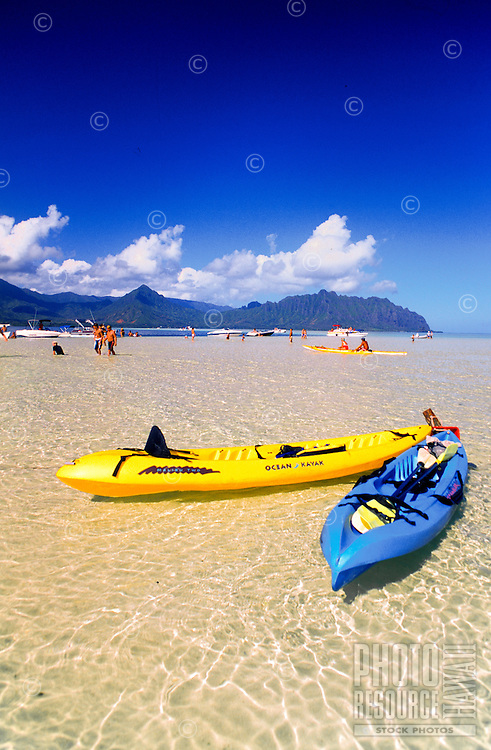 Kayakers rest on the iviting sand bars and calm waters of Kaneohe Bay, Oahu.
