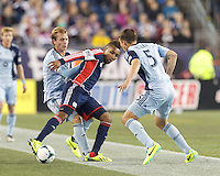 New England Revolution forward Juan Agudelo (10) dribbles as Sporting Kansas City defender Seth Sinovic (15) defends. In the first game of two-game aggregate total goals Major League Soccer (MLS) Eastern Conference Semifinal series, New England Revolution (dark blue) vs Sporting Kansas City (light blue), 2-1, at Gillette Stadium on November 2, 2013.