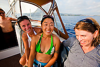 Young women enjoying a sailboat cruise on the west side of Oahu