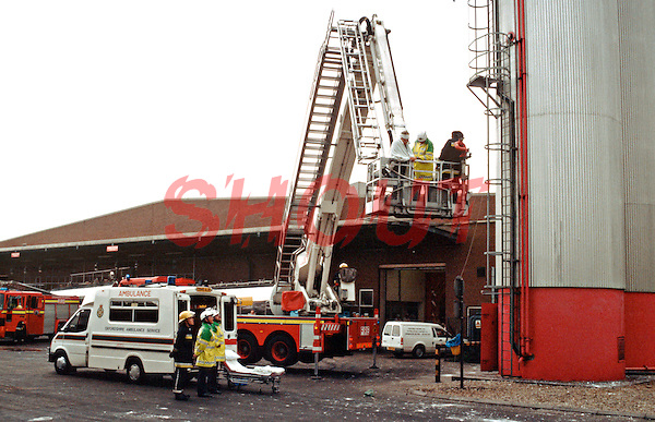 Hydraulic platform fire engine performing a rescue from a silo. The firefighters, paramedics and the casualty are in the cage at the end of the boom. The workman fell down into the sugar silo and was knocked unconscious. The firefighters, wearing breathing apparatus, had to absail down inside the silo and haul him out by means of a rope sling. The ambulance crew on the ground are waiting to take him to hospital...© SHOUT. THIS PICTURE MUST ONLY BE USED TO ILLUSTRATE THE EMERGENCY SERVICES IN A POSITIVE MANNER. CONTACT JOHN CALLAN. Exact date unknown.john@shoutpictures.com.www.shoutpictures.com..