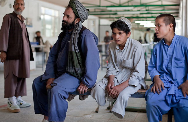20 August 2011, Kabul, Afghanistan:  Saida Aziz (centre,12)sits with his father Said. The boy lost both his legs after a coalition helicopter fired two shells killing 12 of his fathers sheep and the second slicing his legs off before exploding outside Bagram air base where he was herding sheep. He is at the International Committee of the Red Cross (ICRC) Orthopaedic Centre in Kabul where victims of war as well as the disabled, are fitted with artificial limbs, hand made on the compound. Saida is being rehabilitated with new legs. Picture by Graham Crouch for The Australian Magazine