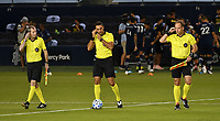 KANSAS CITY, KS - OCTOBER 07: The refereeing team, (L-R) Cory Richardson, Marcos de Oliveira and Brian Poeschel split off to their assignments before the match between Sporting KC and Chicago Fire FC before a game between Chicago Fire and Sporting Kansas City at Children's Mercy Park on October 07, 2020 in Kansas City, Kansas.