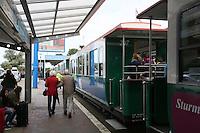 Touristen auf dem Weg zur Borkumer Inselbahn am Hafen von Borkum