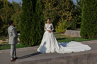 Armenia. Yerevan. A married couple stands in the park outside of Saint Gregory the Illuminator Cathedral, also known as the Yerevan Cathedral is currently the largest cathedral of the Armenian Apostolic Church in the world. Yerevan, sometimes spelled Erevan, is the capital and largest city of Armenia. 10.10.2019 © 2019 Didier Ruef