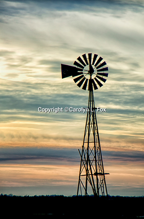 An old fashioned windmill sits in a field in the midwest.