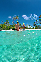 Couple ready to go snorkling off a beautiful beach in Aitutaki Lagoon, Cook Islands, in the South Pacific.  Model Released.