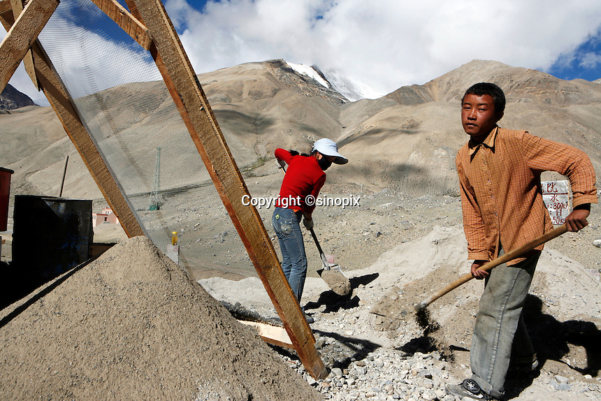 """Fifteen year old Chisu sifts rocks and stones to build the road to Everest Base Camp.China started building a controversial 67-mile """"paved highway fenced with undulating guardrails"""" to Mount Qomolangma, known in the west as Mount Everest, to help facilitate next year's Olympic Games torch relay."""