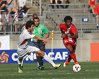 Belize forward Michael Salazar (11) on the attack as Cuban defender Jorge Clavelo (5) closes. In CONCACAF Gold Cup Group Stage, the national team of Cuba (white) defeated national team of Belize (red), 4-0, at Rentschler Field, East Hartford, CT on July 16, 2013.