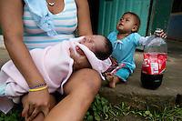 Huani Eromenga, 21, and her daughters, Rafaela (Wenonka) Ahua (2), and Juanilu  (Mencamo) Ahua (2 weeks), drinking Coca-Cola in the Waorani (Huaroni) community of Guiyero.