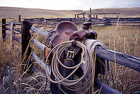 Cowboy's Horse Saddle and Lasso hanging over a Rail Fence around a Ranchland Corral, Thompson Okanagan Region, BC, British Columbia Canada