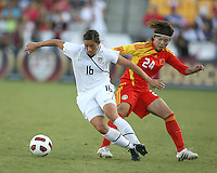Ali Krieger #16 of the USA WNT moves the ball away from Yasha Gu #24 of the PRC WNT during an international friendly match at KSU Soccer Stadium, on October 2 2010 in Kennesaw, Georgia. USA won 2-1.