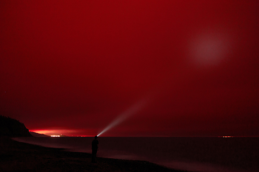 A man searches the red skies with a headlamp along the shore of Ebey Landing, Whidbey Island, Washington State.