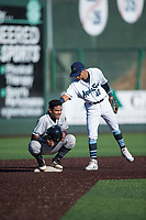 Tri-City Dust Devils catcher Alison Quintero (32) gets a pat on the back from Cesar Izturis Jr. (40) during a Northwest League game against the Everett AquaSox at Everett Memorial Stadium on September 3, 2018 in Everett, Washington. The Everett AquaSox defeated the Tri-City Dust Devils by a score of 8-3. (Zachary Lucy/Four Seam Images)