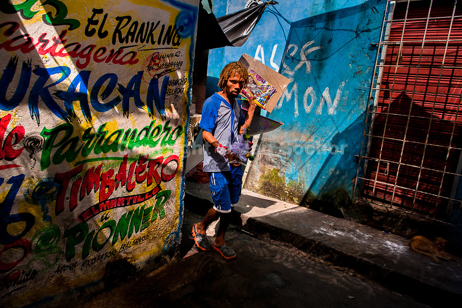 An Afro-Colombian street vendor walks around the wall, covered with Champeta music propaganda, in the market of Bazurto in Cartagena, Colombia, 16 December 2017. Far from the touristy places in the walled city, a colorful, vibrant labyrinth of Cartagena's biggest open-air market sprawls to the Caribbean seashore. Here, in the dark and narrow alleys, full of scrappy stalls selling fruit, vegetables and herbs, meat and raw fish, with smelly garbage on the floor and loud reggaeton music in the air, the African roots of Colombia are manifested.