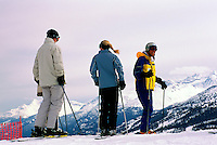 Three Skiers downhill skiing on Whistler Mountain at Whistler Resort, in the Coast Mountains, Whistler, British Columbia, Canada