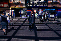 A businessmen crosses a downtown street in Chile's bustling capital and largest city. Approximately three decades of uninterrupted economic growth have transformed Santiago into one of Latin America's most sophisticated metropolitan areas, with extensive suburban development, dozens of shopping malls, and impressive high-rise architecture.
