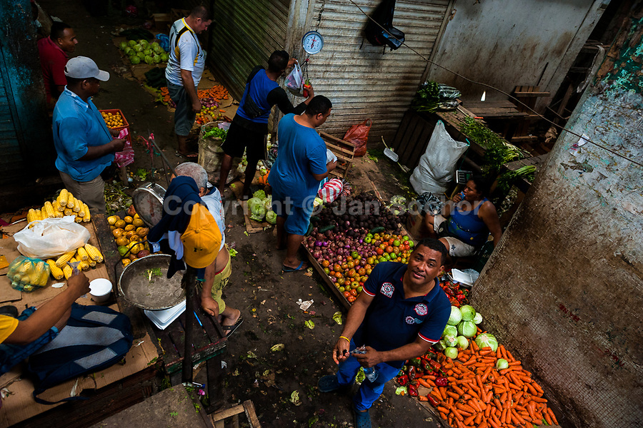 Afro-Colombian men walk along piles of fruits and vegetables while shopping in the market of Bazurto in Cartagena, Colombia, 17 April 2018. Far from the touristy places in the walled city, a colorful, vibrant labyrinth of Cartagena's biggest open-air market sprawls to the Caribbean seashore. Here, in the dark and narrow alleys, full of scrappy stalls selling fruit, vegetables and herbs, meat and raw fish, with smelly garbage on the floor and loud reggaeton music in the air, the African roots of Colombia are manifested.