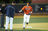 Jack Weiller (3) of the Virginia Cavaliers shakes hands with third base coach Kevin McMullan (44) as he rounds third base after hitting his second home run of the game against the Wake Forest Demon Deacons at David F. Couch Ballpark on May 18, 2018 in  Winston-Salem, North Carolina.  The Cavaliers defeated the Demon Deacons 15-3.  (Brian Westerholt/Four Seam Images)