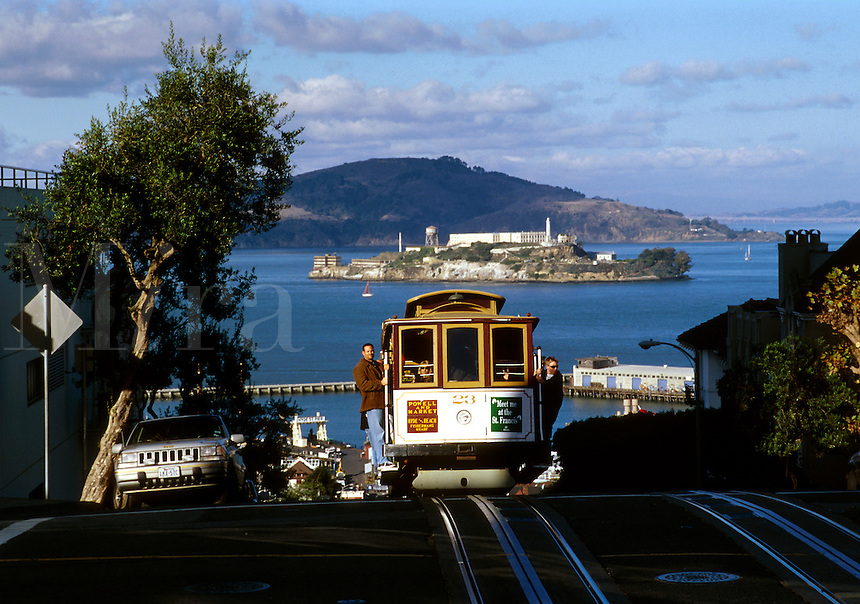 A cable car ascends Hyde Street on Russian Hill with Alcatraz Island and prison in the background. San Francisco, California.