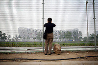 """CHINA. Beijing. A man looks through a fence, trying to catch a glimpse of the new Olympic park. In recent years construction has boomed in Beijing as a result of the country's widespread economic growth and the awarding of the 2008 Summer Olympics to the city. For Beijing's residents however, it seems as their city is continually under construction with old neighborhoods regularly being razed and new apartments, office blocks and sports venues appearing in their place. A new Beijing has been promised to the people to act as a showcase to the world for the 'new' China. Beijing's residents have been waiting for this promised change for years and are still waiting, asking the question """"Where's the new Beijing?!"""". 2008"""