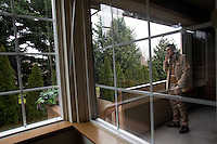 Adil Kheder Nimr, 27, takes a break on the porch of his new apartment in Tukwila, Wash. on January 30, 2017. He and his wife Shatha Sulaiman Kheder, 27, and their son Steven Adil Kheder, 10 months, arrived in the United States as refugees from Iraq on January 19, 2017, the day after Donald Trump was sworn in as the 45th president of the United States. They are concerned about thirteen of their family members still in Iraq. Trump signed an executive order last Friday restricting immigration from seven Muslim countries, suspending all refugee admission for 120 days, and bans all Syrian refugees indefinitely.  (Photo by Karen Ducey)