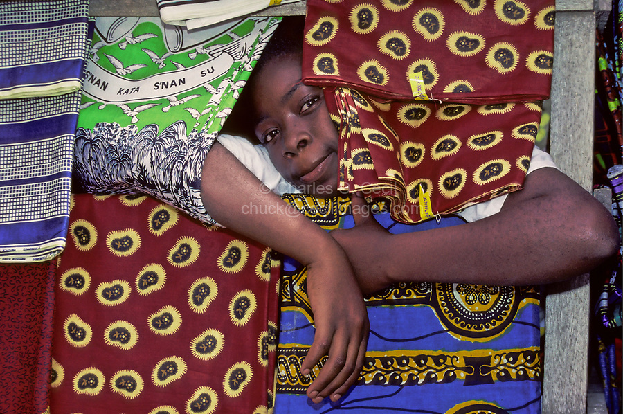 Bondoukou, Ivory Coast, Cote d'Ivoire, West Africa.  Sylvie Koulongo, a Vendor of Fabric, Waits for a Customer in the Market in Bondoukou, Cote d'Ivoire.