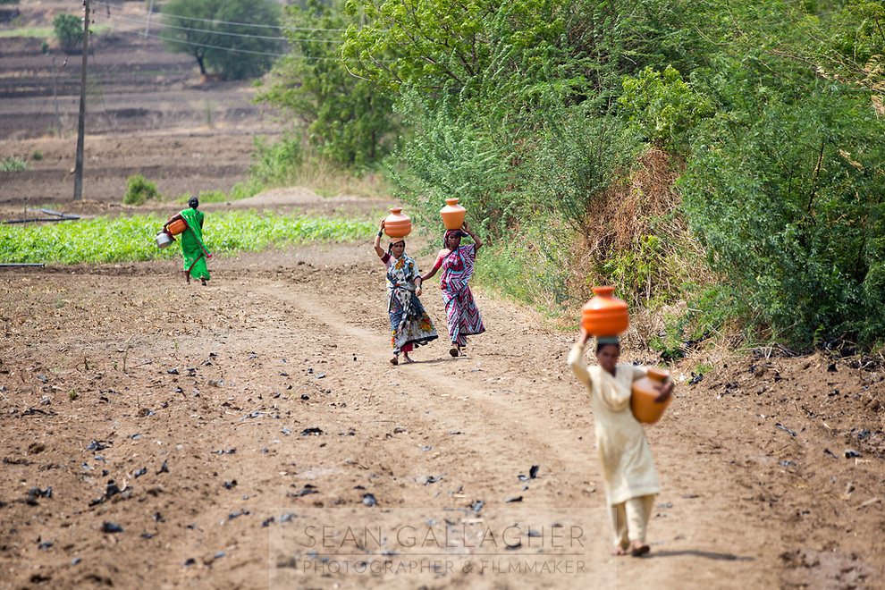 Women carry pots full of water through dried up fields outside the village of Sayyad Ankulga. Only two bore wells now operate near the village, the closest one being over 1 kilometre away from the village centre, forcing villagers to walk through the intense heat multiple times a day to collect water