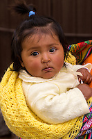 Peru, Cusco.  Young Quechua Girl being Carried on her Mother's  Back.