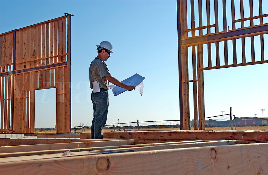 Construction foreman with blueprints on job site.