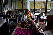 A mother is seen with her malnutritioned child in Maharani Laxmibai Medical College in Jhansi, Uttar Pradesh, India. The Indian government spends $1.4 billion a year - on programs that include weighing newborn babies, counseling mothers on healthy eating and supplementing meals, but none of this is yeilding results. According to UNICEF, some 48% of Indian children, or 61 million kids, remain malnourished, the clinical condition of being so undernourished that their physical and mental growth are stunted. Photo: Sanjit Das/Panos for The Wall Street Journal.Slug: IMALNUT