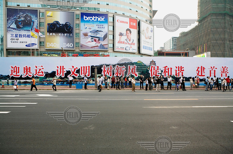 """Commuters waiting below advertising posters for Samsung, Nikon, Brother and Canon electronic goods at a bus stop after work in a busy shopping area. The huge government billboard behind them says """"Welcome the Olympics, be civilised, be positive, promote harmony and build a good capital"""", in reference to the forthcoming 2008 Olympic Games."""