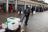 A stallholder pulls a trolley  of fresh vegetables in Doncaster market .