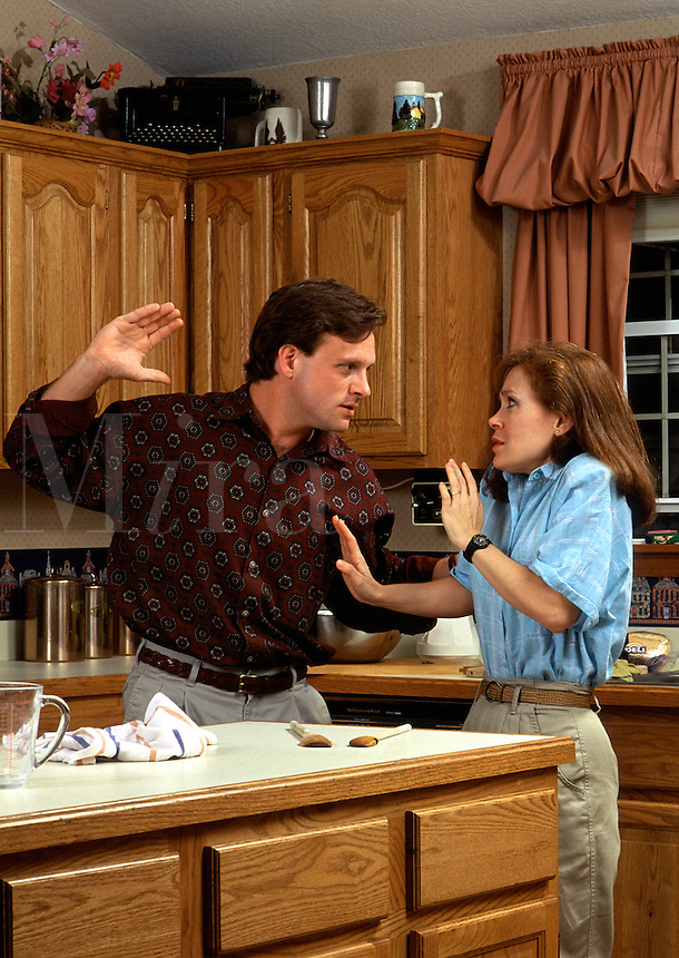 An angry man about to hit his frightened wife.