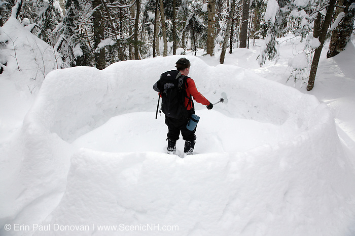 Appalachian Trail...A hiker explores the remains of an snow igloo in the White Mountains, New Hampshire USA during the winter months.