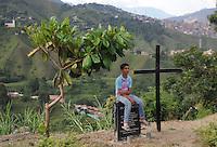 """MEDELLÍN - COLOMBIA, 07-06-2014. Un joven sentado sobre unaplaca conmemorativa por las personas desaparecidas en """"La Escombrera"""", en la Comuna 13 de Medellín, durante una vigilia contra las desapariciones forzadas. En 2002, Medellín fue sacudido por la violencia después de la decisión del Gobierno de recuperar un sector de la ciudad disputada por los paramilitares de derecha y las milicias de izquierda. Según los familiares de las víctimas, en la operación ordenada el 16 de octubre de 2002 por el presidente Álvaro Uribe, decenas de personas murieron, más de 100 personas resultaron heridas, 98 personas desaparecieron y más de 200 familias fueron desplazadas./  A young rest over the commemorative plaque in memory of the missing persons in """"The Dump"""" in Comuna 13 in Medellín, during a vigil against forced disappearances. In 2002, Medellín was rocked by violence following the government's decision to recover a part of the city disputed by right-wing paramilitaries and leftist militias. According to relatives of the victims, the orderly operation on October 16, 2002 by President Alvaro Uribe, dozens of people were killed, over 100 people were injured, 98 people missing and more than 200 families were displaced. Photo: VizzorImage/Luis Rios/STR"""