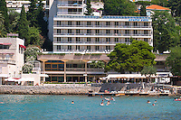 Hotel, restaurant with terrace, sea and beach, people swimming. Hotel and restaurant Kompas. Uvala Sumartin bay between Babin Kuk and Lapad peninsulas. Dubrovnik, new city. Dalmatian Coast, Croatia, Europe.
