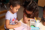 Education preschool girl writing name on sign-in sheet in morning watched by classmate