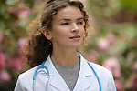 Portrait of a young woman doctor, medical practitioner with an aspiring thoughtful look, career in natural medicine, healthcare as a physician. The woman is wearing a lab coat in natural outdoor settings in a garden with beautiful blossoming flowers
